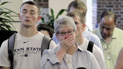 Susan DelPonte, center, of State College, a Penn State employee and student advocacy specialist, reacts Monday in the Hetzel Union Building on the Penn State campus as the NCAA sanctions against the Nittany Lions are televised.