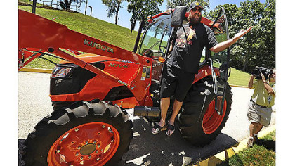 Steelers defensive lineman Brett Keisel arrives at training camp in a bright orange Kubota tractor Wednesday afternoon at Saint Vincent College in Latrobe.