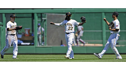 Pirates Alex Presley, Andrew McCutchen and Gorkys Hernandez celebrate after defeating the Cubs Wednesday afternoon.