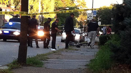Pittsburgh police officers look over the scene where a bicyclist died early Wednesday morning after being struck by a car in Point Breeze.
