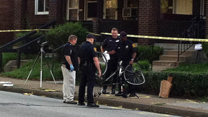 Pittsburgh police officers examine the bicycle that was struck by a white car early Wednesday morning.