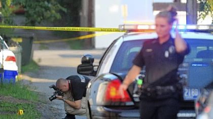 Police investigate the scene where Monaca Officer Alan Shaffer was shot in the leg Wednesday during the foot pursuit in Monaca of a suspect who had earlier robbed a Cricket store. Here, an officer photographs the locations of bullet casings in the alley where Officer Shaffer was shot.  Police have the suspect in custody.