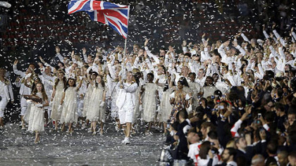 Great Britain's Chris Hoy carries the national flag as confetti surrounds the team during the Opening Ceremony at the 2012 Summer Olympics, Friday, July 27, 2012, in London.