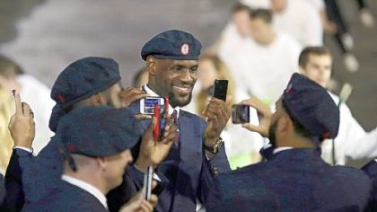 Professional basketball player LeBron James takes pictures with members of the the United States' Olympic team during the Opening Ceremony at the 2012 Summer Olympics, Friday, July 27, 2012, in London.