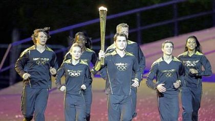 Torchbearers run during the Opening Ceremony at the 2012 Summer Olympics, Friday, July 27, 2012, in London.