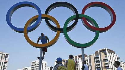 Ukrainian boxer Alexander Usik climbs the Olympic rings for photos at the Athletes' Village at the Olympic Park. The opening ceremonies for the 2012 London Olympics will be held today.