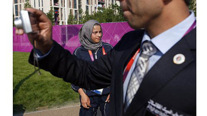 A man takes a photo near Tahmina Kohistani, Afghanistan's only female athlete, after attending the Olympic Team Welcome Ceremony at the Athletes' Village.