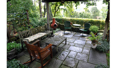 The flagstone patio is shaded by a pergola.