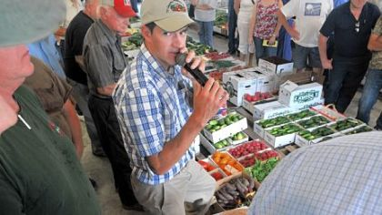 Auctioneer Andrew Yoder watches for a higher bid on a box of beets as he deals with the merchandise at the Tri County Produce Auction.