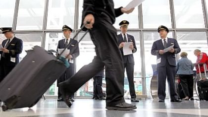 United Airlines pilots pass out leaflets to passengers at O'Hare International Airport on May 7 to get their point across United's outsourcing of U.S. jobs.