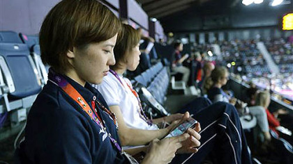 Japan's Miyuki Maeda checks at her iPhone as she watches badminton matches in progress at the Summer Olympics, Tuesday, July 31, 2012, in London. The 2012 games are being shaped, shaken and indisputably changed by the social media revolution.