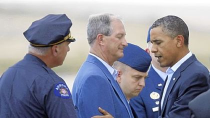 President Barack Obama greets Aurora&#039;s Mayor Steve Hogan, center, and police Chief Dan Oates, left, Sunday.