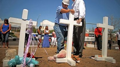 Greg Zanis, left, a carpenter from Aurora, Ill., prays with Aurora, Colo., Mayor Steve Hogan at the 12 crosses Mr. Zanis made for a makeshift memorial to the victims of the weekend&#039;s mass shooting in suburban Denver.