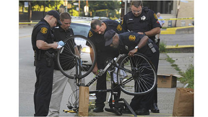 Police officers examine the bike belonging to James Price of Homewood, who was struck and killed by a hit-and-run driver on Penn Avenue July 25.