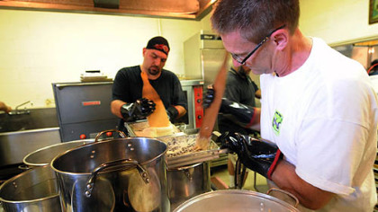 Parish members Tim Polas, left, and John Kirish, right, scrape halushky batter into boiling water to make the church's signature dish -- potato dumpling halushky at St. John the Baptist Orthodox Church in Ambridge.