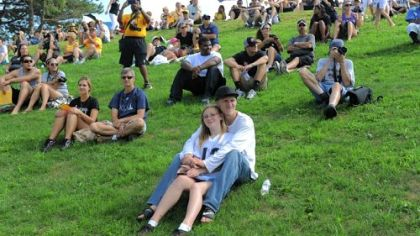 Brandy Gruber and Jeremy Hilss of Freeport sit in front on the grassy hillside to watch the first public practice at Steelers training camp at Saint Vincent College in Unity on Friday.