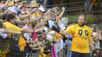 Steelers defensive lineman Brett Keisel waves to the fans as he makes his way to the field before the start of workouts Friday at Steelers training camp at Saint Vincent College near Latrobe.