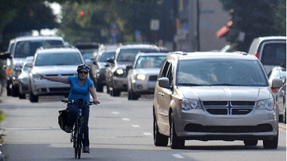 A woman bicycles through Wednesday evening's rush-hour traffic on Penn Avenue near Braddock Avenue.