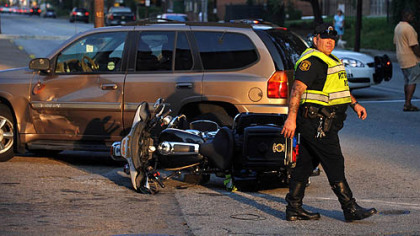 Police direct traffic around the scene of an accident involving an officer riding a motorcycle Thursday on Penn Avenue at its intersection with North Lexington.