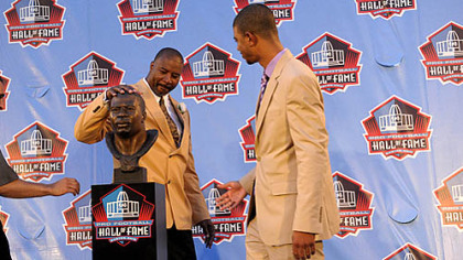 Chris Doleman pats his bust as his son Evan Doleman stands by after the former Pitt standout was welcomed into the Pro Football Hall of Fame Saturday night in Canton, Ohio.