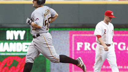 The Pirates' Michael McKenry rounds the bases past Cincinnati Reds shortstop Zack Cozart after McKenry hit a solo home run in the second inning.
