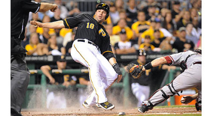 Neil Walker looks for the call as he slides into home safely.