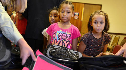Aaliyah Burke, 6, left, and Olivia Robertson, 6, pick out backpacks during a giveaway Thursday at the Salvation Army's New Kensington Worship and Service Center.