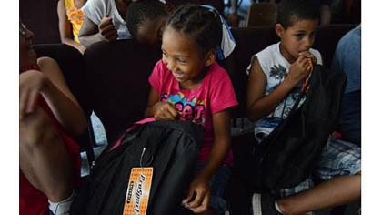 Aaliyah Burke, 6, looks through her new backpack after a giveaway Thursday at the Salvation Army?s New Kensington Worship and Service Center.