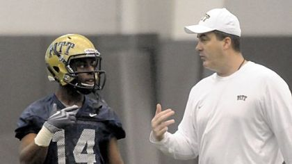 New Pitt head football coach Paul Chryst works with wide receiver Ronald Jones.