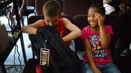 Wesley Filer, 10, and Aaliyah Burke, 6, discuss a school supply trade after a backpack giveaway Thursday at the Salvation Armys New Kensington Worship and Service Center.