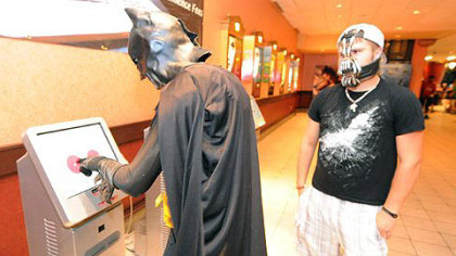 Dustin Briggs, dressed as Batman, buys a ticket to the midnight showing of &quot;The Dark Knight Rises&quot; at AMC Loews Waterfront, while Tanner Kefover, dressed as Bane, looks on.
