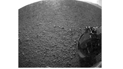 "One of the first images taken by NASA's Curiosity rover, which landed this morning on Mars. The image was taken through a ""fisheye"" wide-angle lens. The clear dust cover that protected the camera during landing has been sprung open. Part of the spring that released the dust cover can be seen at the bottom right, near the rover's wheel."