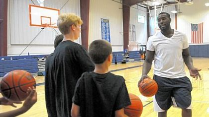 DeJuan Blair of the NBA San Antonino Spurs explains a drill for campers at his basketball day camp at Aquinas Academy in Hampton.