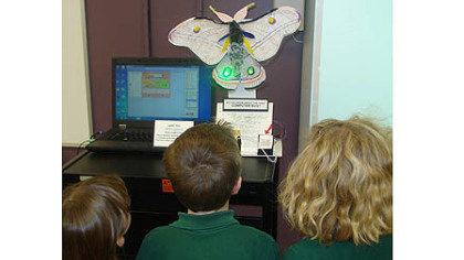 A group of children look at the moth robot and the computer where the program runs.