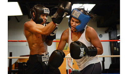 Jennifer Dugwen Chieng takes a hit from Amonte Eberhardt, 21, as they spar Tuesday at the Third Avenue Gym. Ms. Chieng says she usually spars with men as part of her training routine.