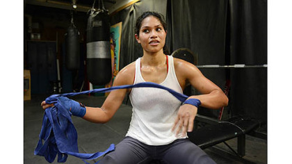 Jennifer Dugwen Chieng unwraps her hands Tuesday after her workout at the Third Avenue Boxing Gym in Downtown Pittsburgh.