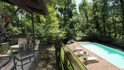 A covered rear deck looks out over the pool and wooded yard.