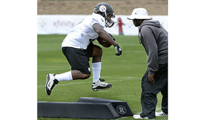 Running backs coach Kirby Wilson puts Will Johnson through his paces Saturday at Saint Vincent College in Latrobe.