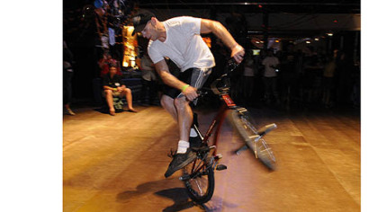 Val Naso does some tricks on a BMX bike.