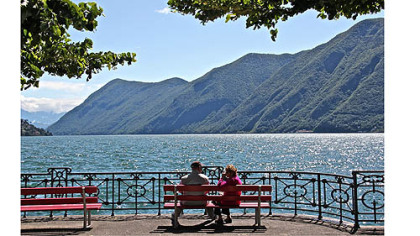 A couple takes in the view from the promenade, Lago Lugano, Switzerland.