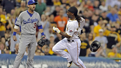 The Pirates&#039; Andrew McCutchen scores against the Dodgers&#039; A.J. Ellis on a double by Garrett Jones in the third inning.