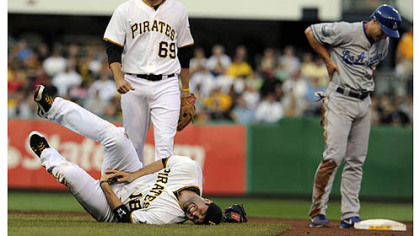 The Pirates' Neil Walker fell to the ground in pain after getting an injury to his right hand after a double play attempt on the Dodgers' Mark Ellis in the first inning at PNC Park Wednesday night.