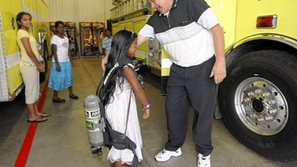 Regina Anand, 8, from Marshall, tries on an oxygen tank with fireman John Ashbaugh during a tour of the station.  Regina donated the money she received at her first communion party to the Marshall Township Volunteer Fire Department.