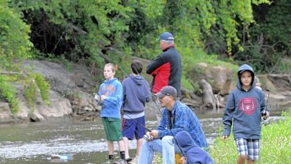 Contestants on Saturday in Heidelberg's first fishing tournament along Chartiers Creek included Bill Puccio of Scott, sitting, and his sons, David Puccio, 11, squatting next to his father, and Tyler Puccio, 9, at far right.