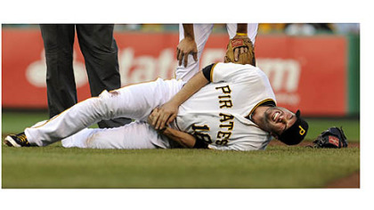 Pirates' Neil Walker writhes in pain after getting an injury to his right hand after a double play attempt on Dodgers' Mark Ellis.